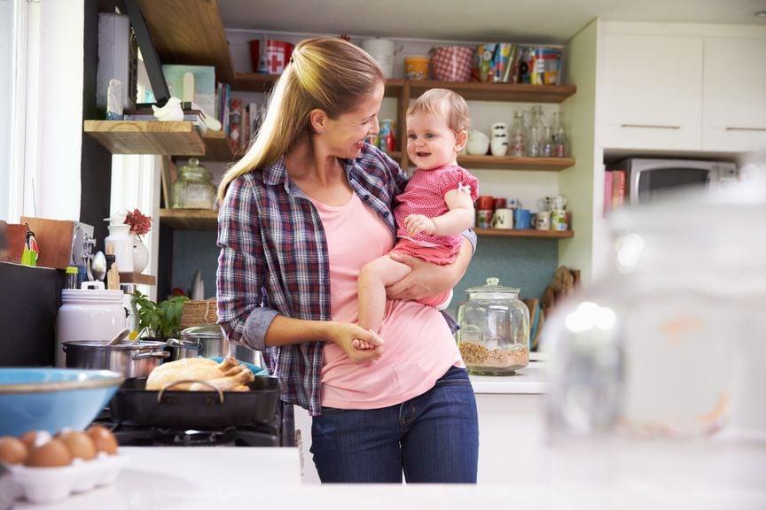 Mutter, in der Küche, hält Baby auf der Hüfte