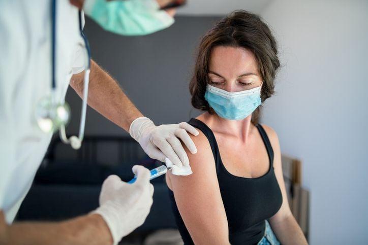 Frau bekommt Impfung mit Spritze