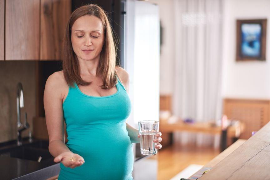 Schwangere mit Wasserglas und Vitaminkapseln in der Hand
