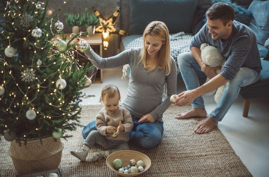 Familie schmückt den Weihnachtsbaum,[Translate to FR:] IStock 861249950