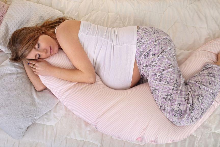 Schwangere in Seitenlage mit Stillkissen