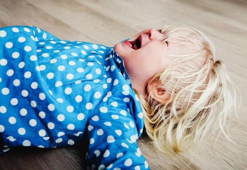 Mädchen liegt in einem Wutanfall schreiend auf dem Boden