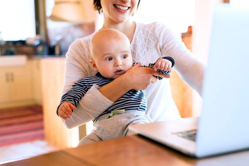 Mutter mit Baby vor dem Laptop