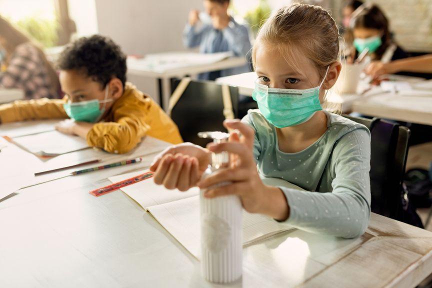 Schulkinder mit Maske und Desinfektionsmittel