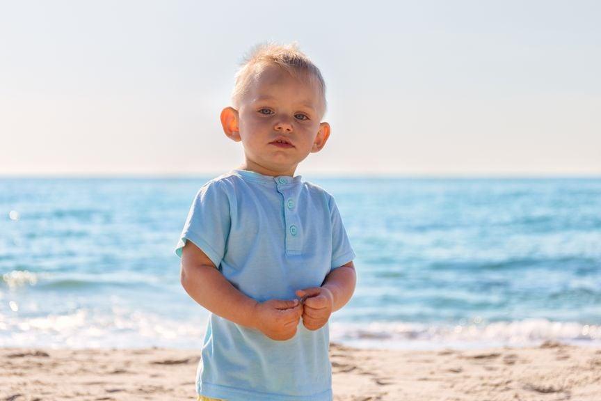 Junge mit abstehenden Ohren am Strand
