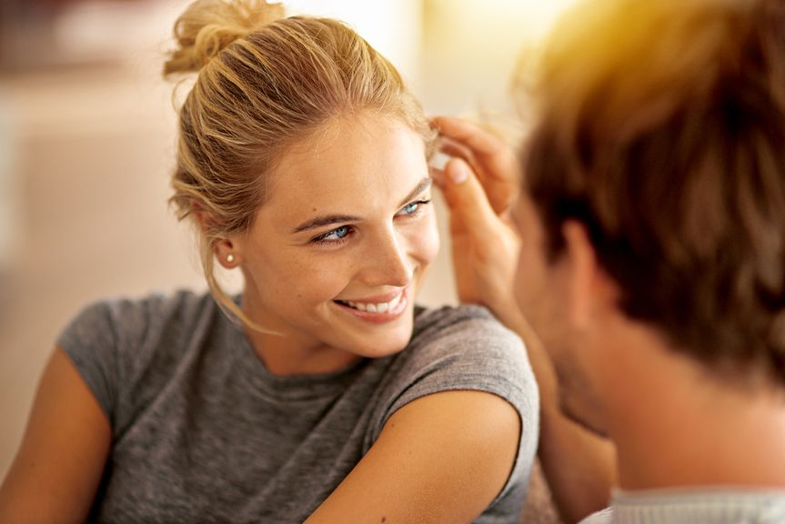 Mann streicht Frau zärtlich durchs Haar
