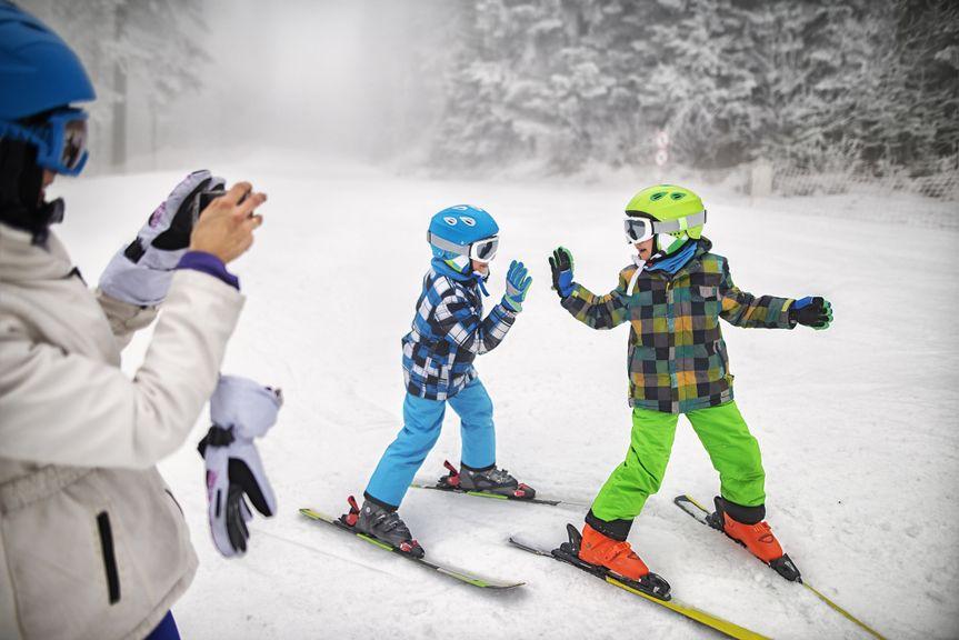 Mutter fotografiert Kinder beim Skifahren
