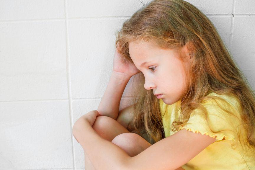 Trauriges Mädchen sitzt an die Wand gelehnt