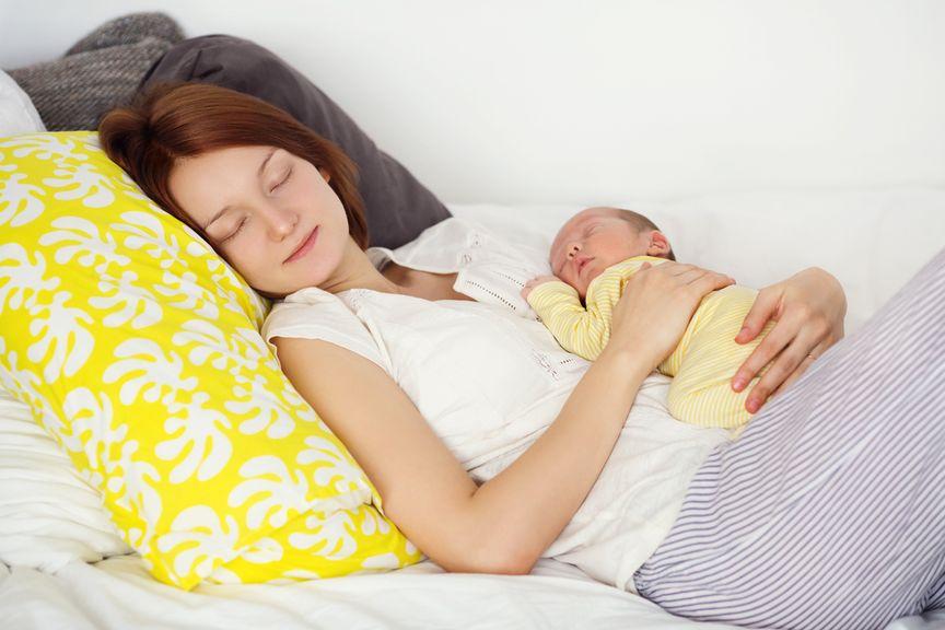 Mutter schläft mit Baby auf dem Bauch