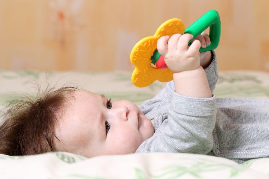 liegendes Baby mit Greiffspielzeug