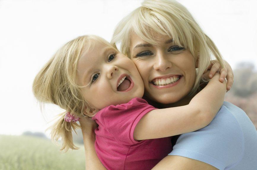 Tochter umarmt lachend ihre Mutter