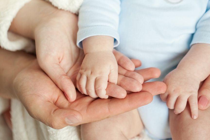 Vater, Mutter und Babyhände liegen aufeinander