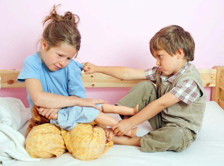 Geschwister streiten auf dem Bett