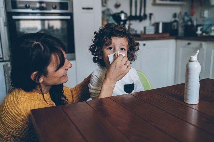 Mutter putzt Kind die Nase