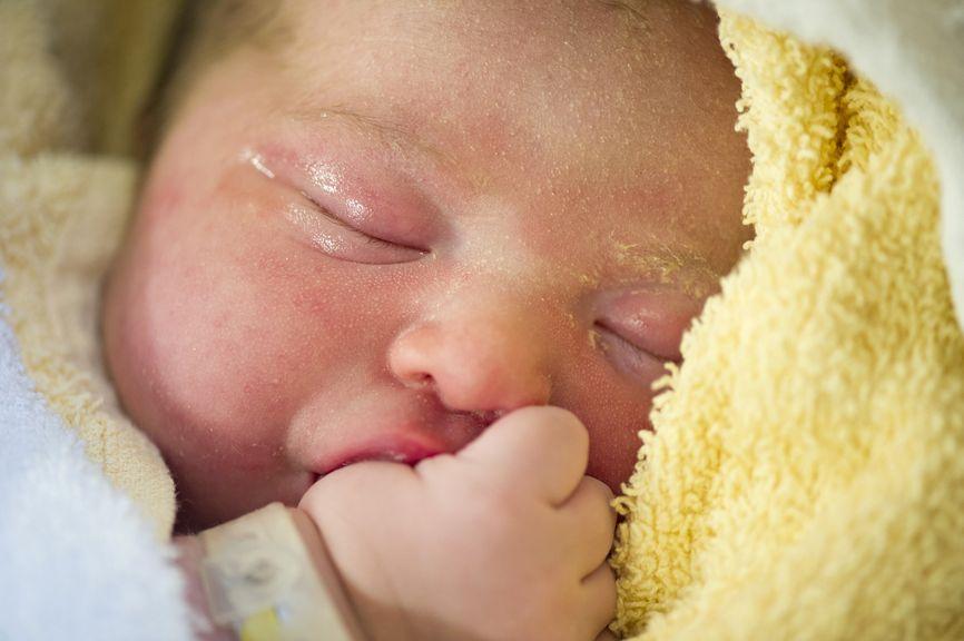 Neugeborenes saugt am Daumen