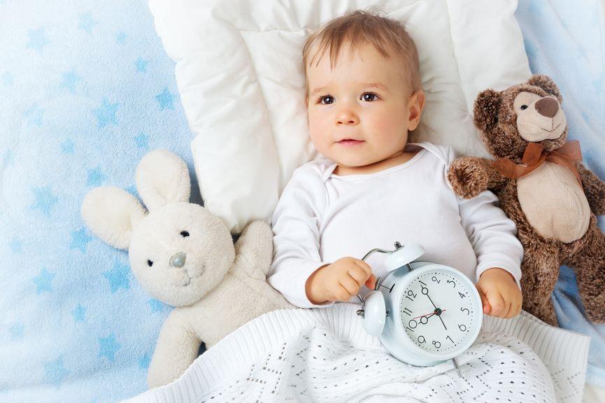 Baby im Bett mit Plüschtieren und Wecker