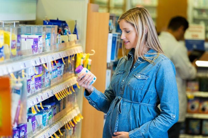 Schwangere vor einem Regal mit Nahrungsergänzungsmitteln