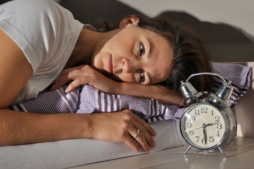 Frau liegt im Bett und schaut auf den Wecker