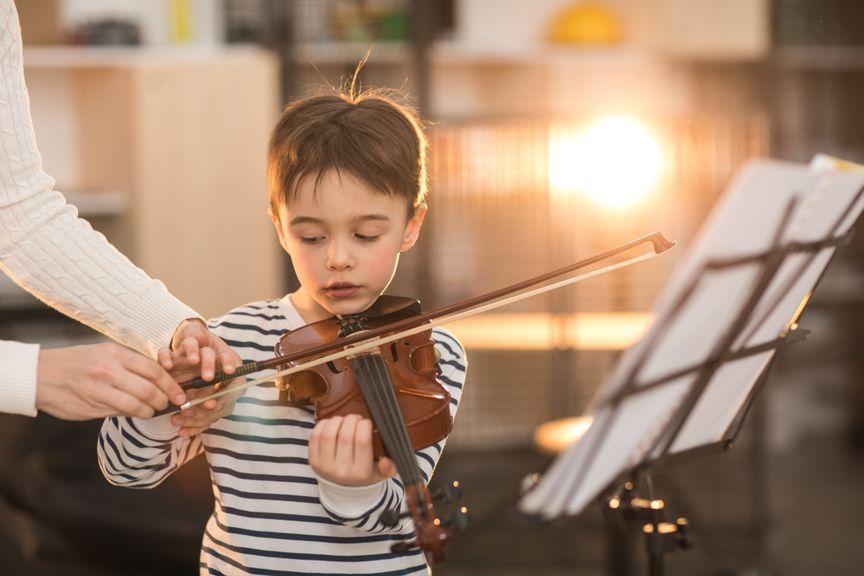 Musiklehrer korrigiert die Haltung des Jungen beim Geigenspiel