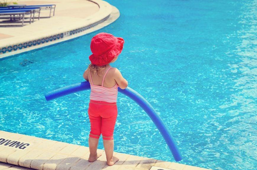 Mädchen mit der Schwimmhilfe am Schwimmbadrand