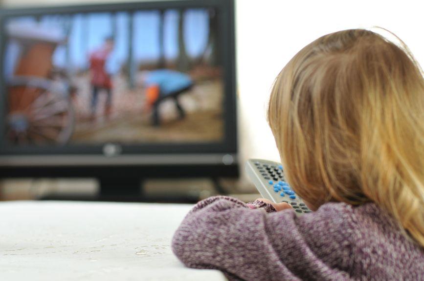 Kind vor dem Fernsehen mit Fernbedienung