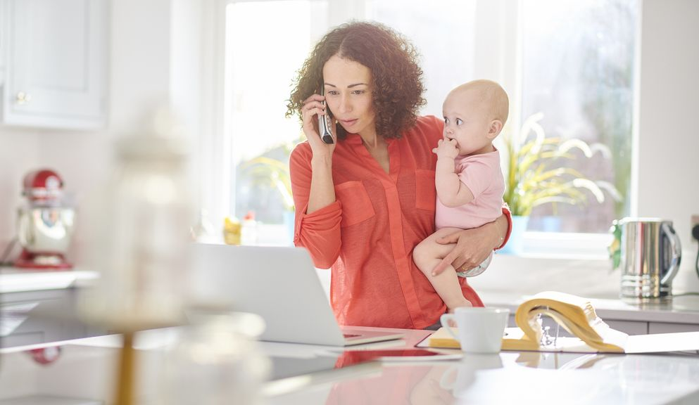 Mutter mit Baby auf dem Arm am Beratungstelefon