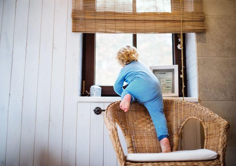 Kind klettert vom Sessel auf die Fensterbank