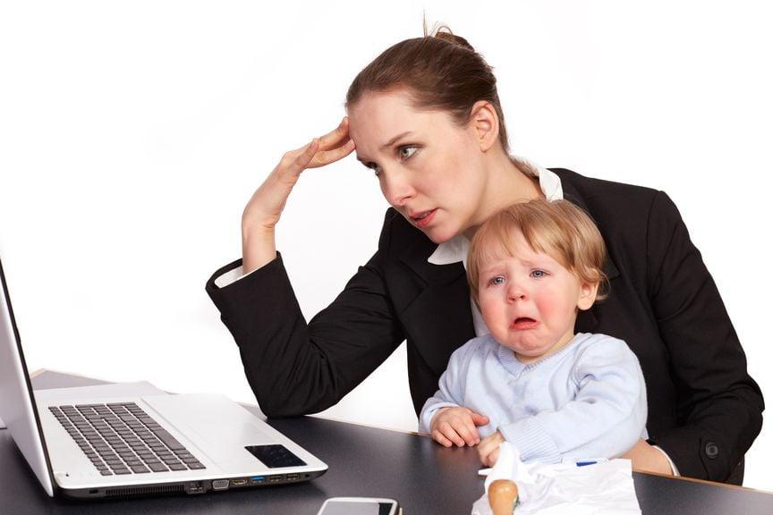 Mutter am Laptop mit weinendem Kind auf dem Schoss