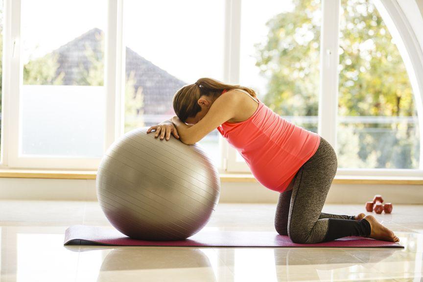 Schwangere stützt sich auf Gymnastikball