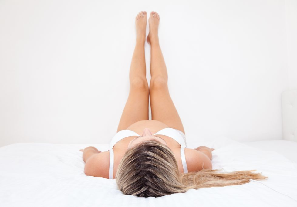 Liegt auf dem Bett und stützt Beine an der Wand ab