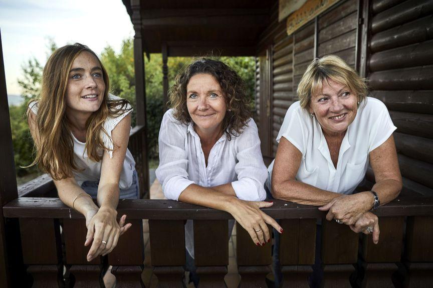 drei Frauen am Geländer eines Holzhauses