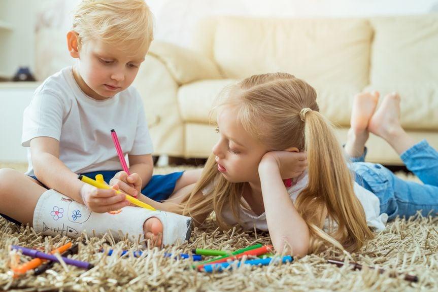 Schwester bemalt den Gips ihres kleinen Bruders