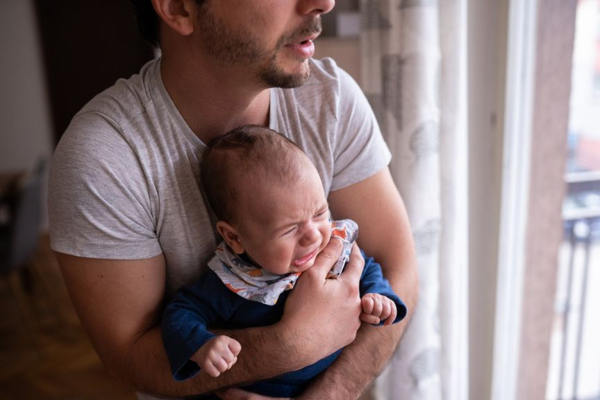 Vater trägt weinendes Baby