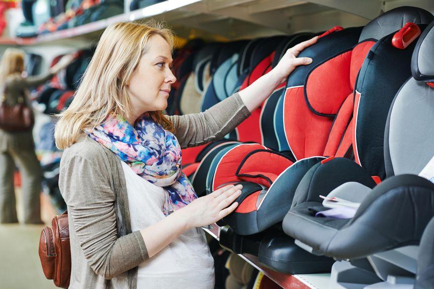 Schwangere schaut sich Kinderautositze an