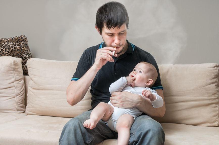 Vater mit Baby auf dem Schoss raucht