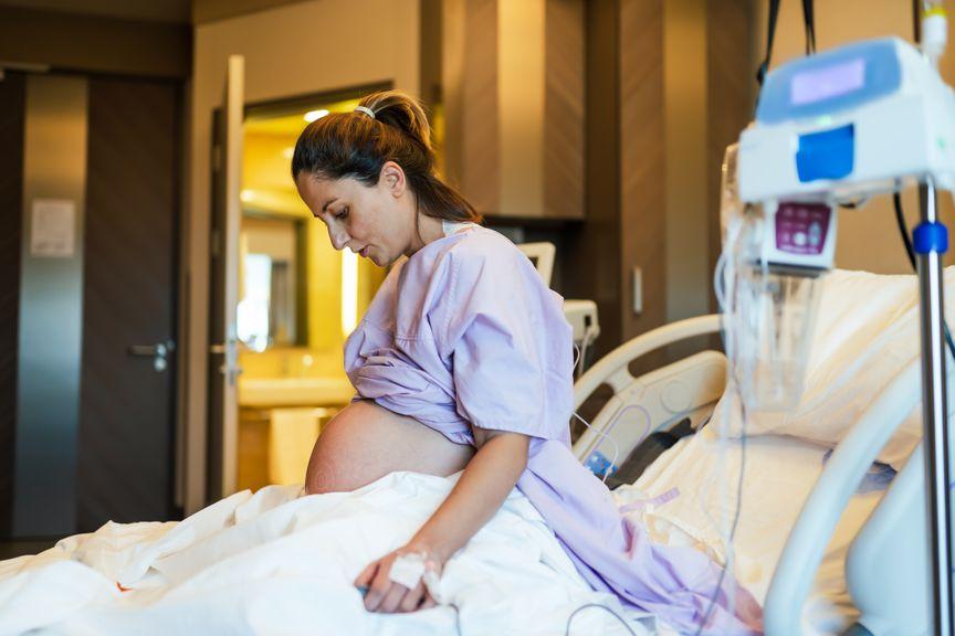 Schwangere sitzend im Spitalbett