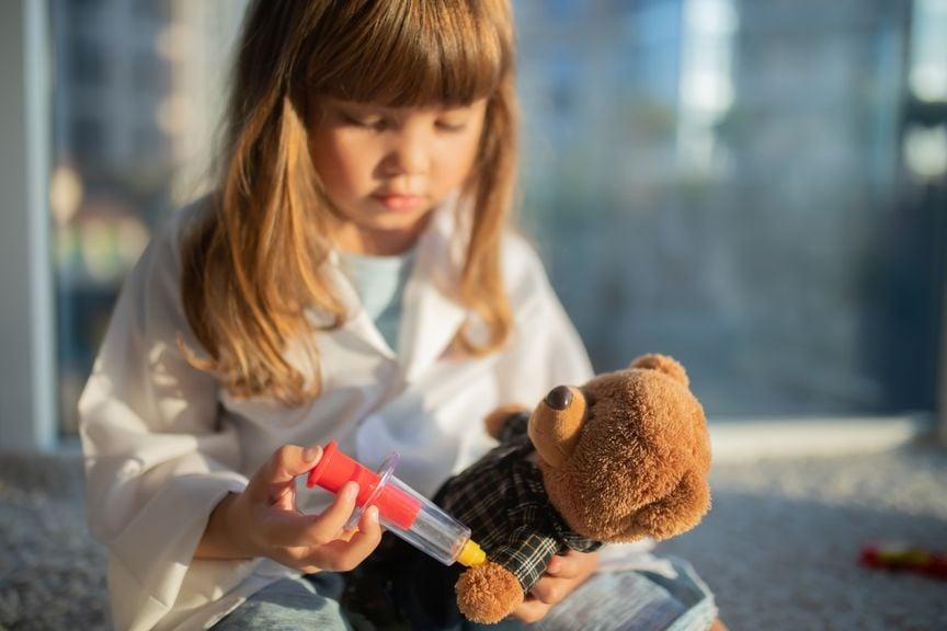 Mädchen gibt ihrem Teddybär eine Spritze