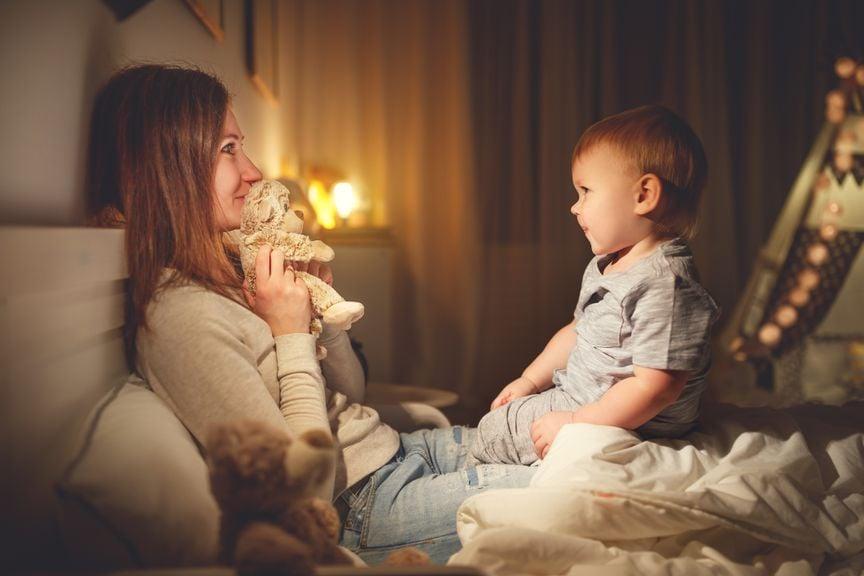 Mutter mit Plüschtier und Baby im Bett