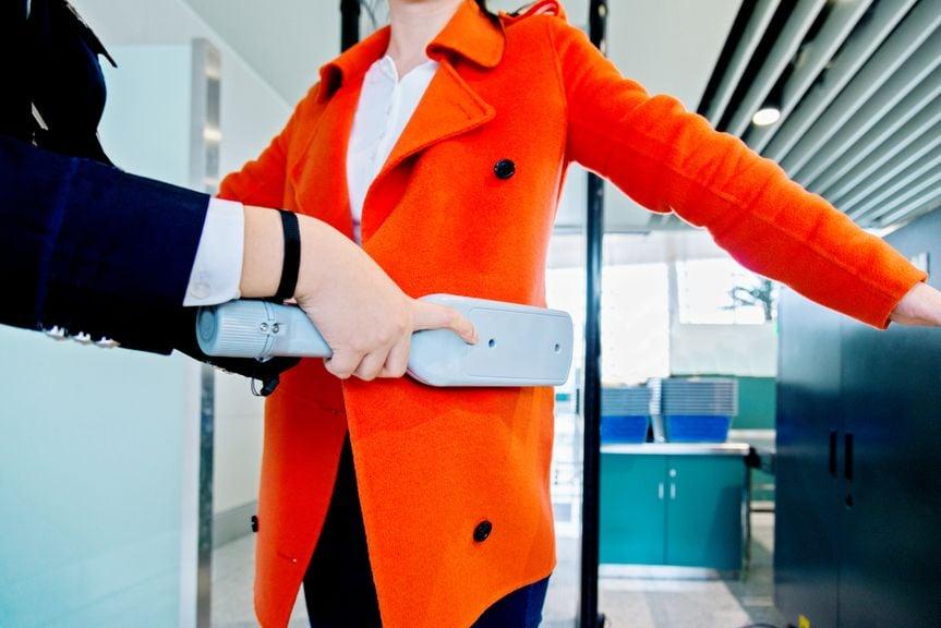 Frau wird am Flughafen mit Metalldetektor kontrolliert