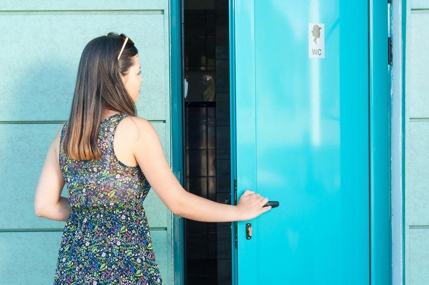 Frau öffnet die Tür einer öffentlichen Toilette
