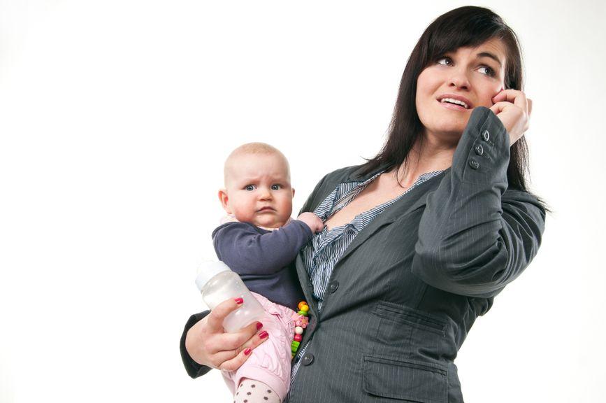 Frau mit Baby auf dem Arm am telefonieren