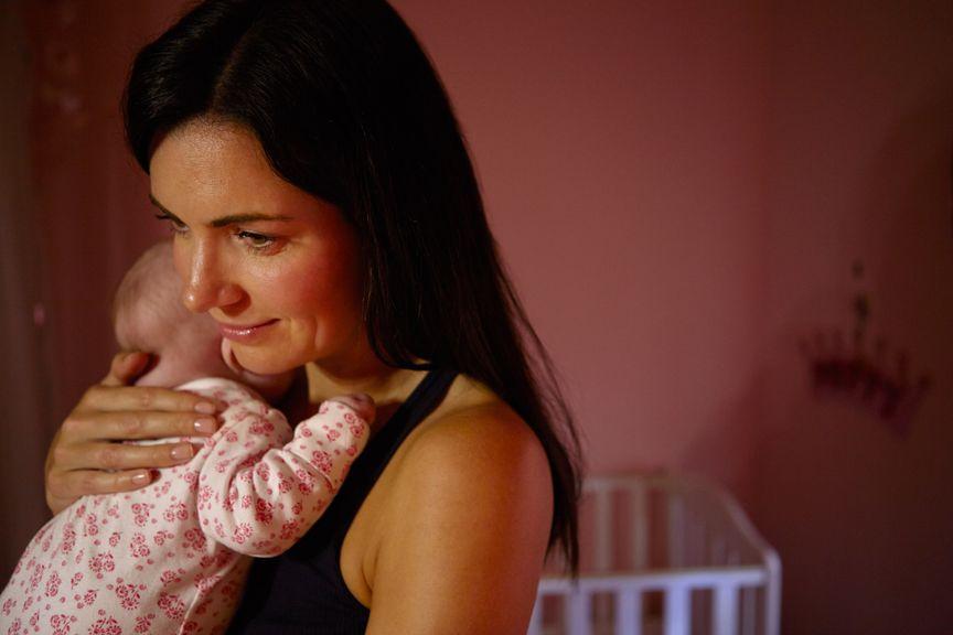 Mutter hält nachts ihr Baby aufrecht im Arm