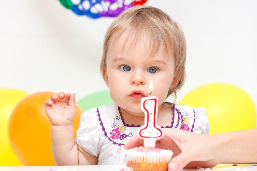 Baby mit Geburtstagskerze