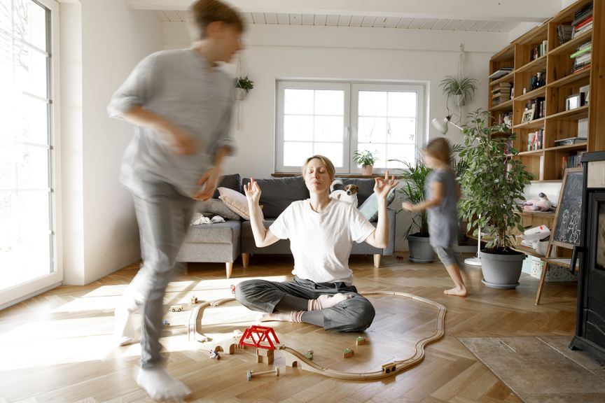 Kinder spielen im Wohnzimmer, Mutter macht Yoga