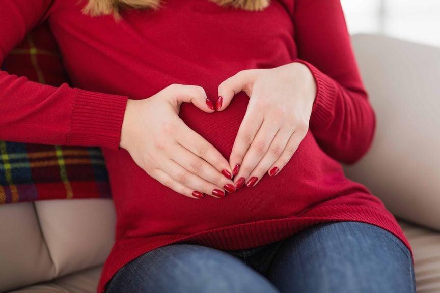 Schwangere formt ein Herz mit ihren Händen auf ihrem Bauch