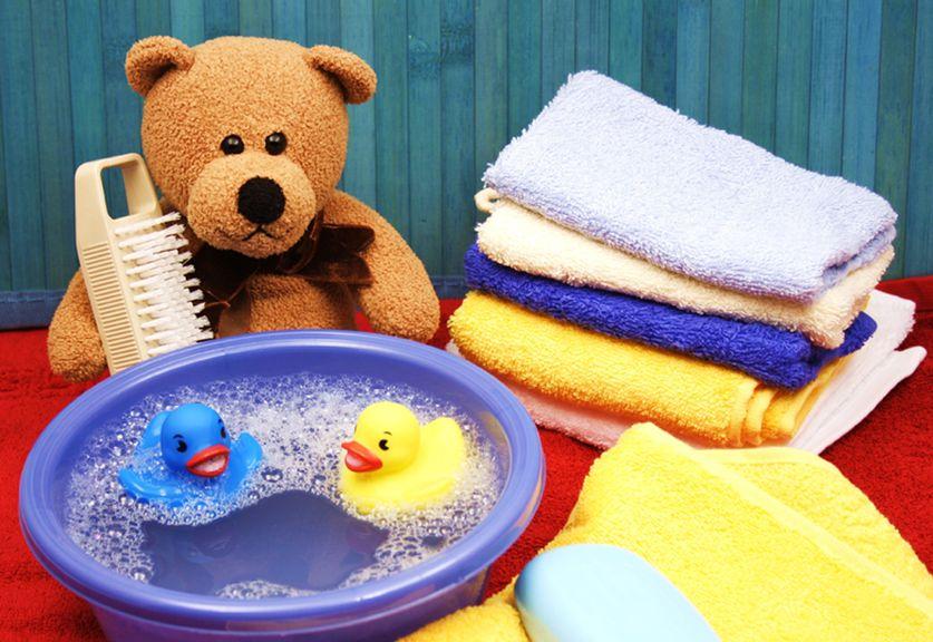 Plastikbecken mit Enten, Teddybär und Handtüchern