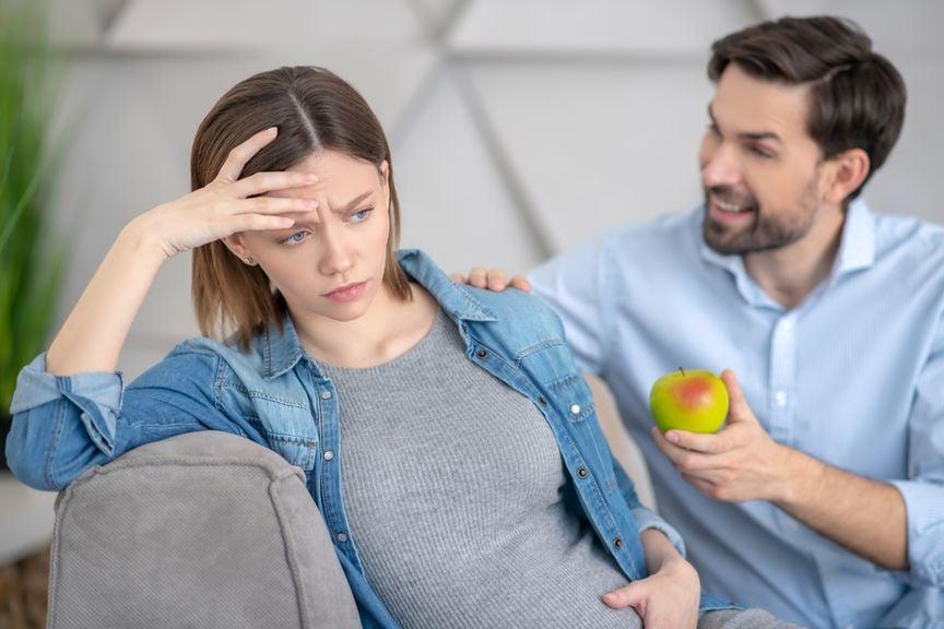 Mann bietet seiner schwangeren Frau einen Apfel an