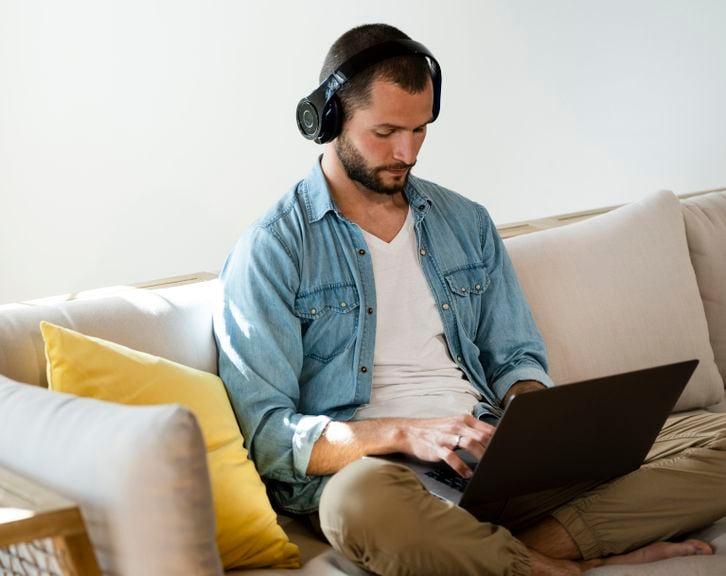 Mann mit Laptop auf dem Sofa