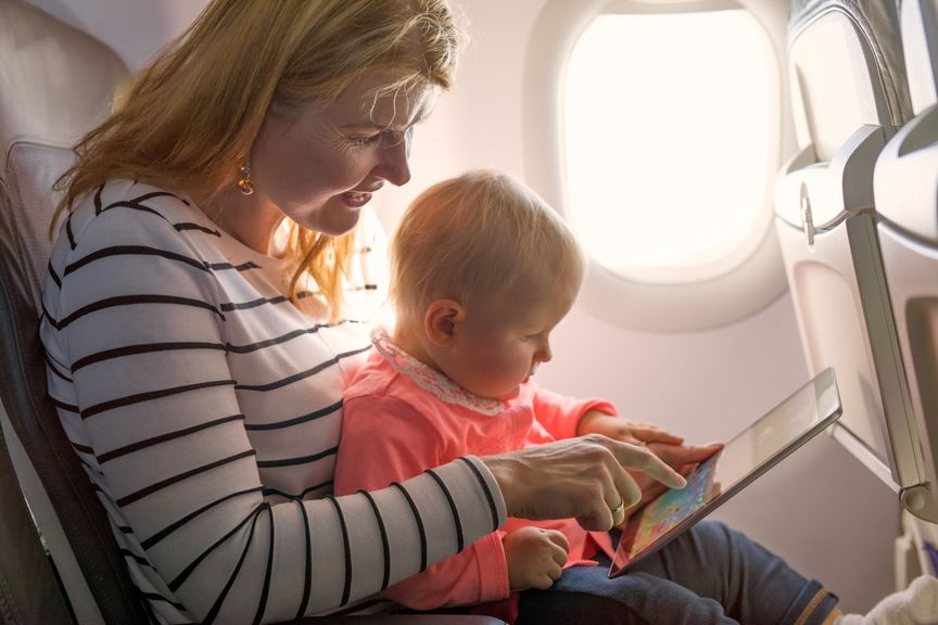 Mutter mit Baby im Flugzeug schauen Bilderbuch an