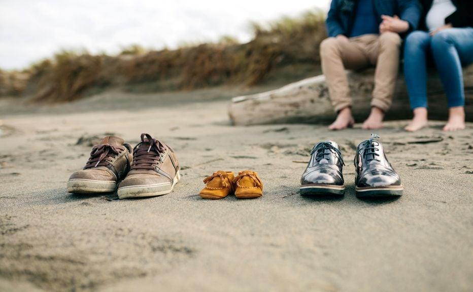 Schuhe von Eltern und Baby am Strand